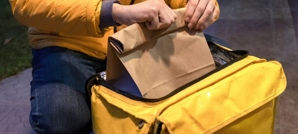 Delivery man in yellow jacket opening yellow backpack and taking a bag with order